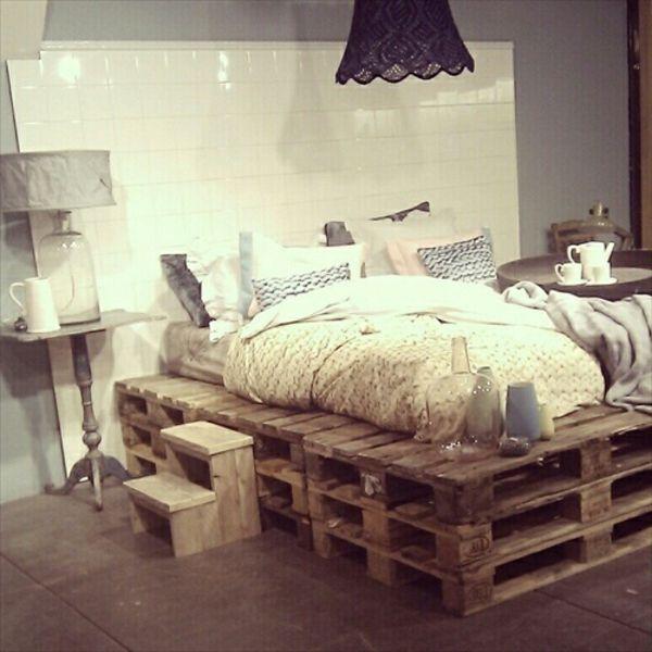 kleines schlafzimmer mit einem bett aus paletten und einem schwarzen kronleuchter