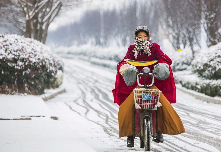 Seorang perempuan mengendarai sepeda listriknya saat turun salju di Lianyungang, Jiangsu, China.