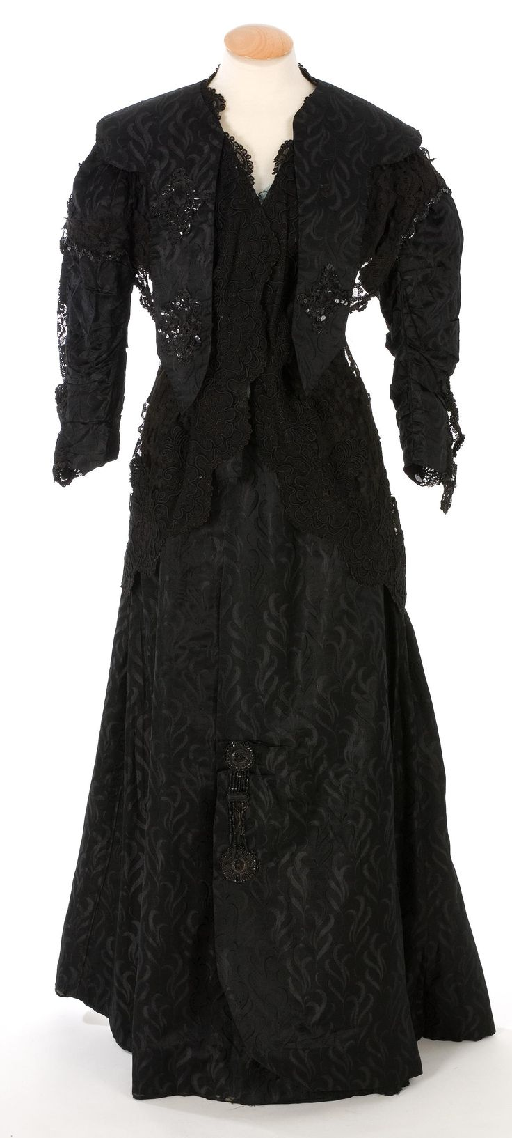 Black silk jaquard dress in 3 pieces, ca. 1900-14, trimmed with jet beads, sequins, and black mechanical lace. Closes with 14 hooks/eyes. Boned bodice lined with sea green printed cotton; skirt lined with brown cotton taffeta. From IMATEX; click through for huge high-definition photo. (Click Pictures, then Extend Image.)