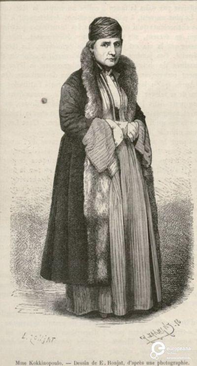 """Η κυρία Κοκκινοπούλου με φορεσιά από την Καλαμάτα. Επιγραφή: """"Mme Kokkinopoulos - Dessin de E.Ronjat, d' après une photographie"""". Υπογραφές: """"E.RONJAT"""", """"CH.BARANT"""". Από το περιοδικό """"Le Tour du Monde"""", Paris, 1877. Δημιουργός: Le Tour du Monde. Ημερομηνία Δημιουργίας: 1877. Συλλέκτης: Peloponnesian Folklore Foundation Ίδρυμα: Europeana Fashion. Συλλέκτης: Peloponnesian Folklore Foundation Ίδρυμα: Europeana Fashion"""