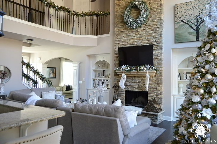 Two story living room with neutral, silver, and gold Christmas decor and large wreath on stone fireplace