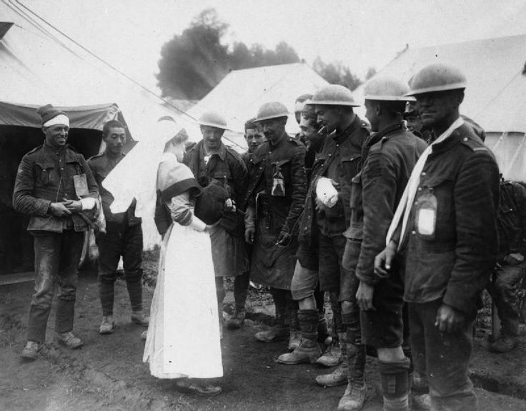 BATTLE SOMME 1 JULY - 18 NOVEMBER 1916 (CO 913)   Wounded Canadian soldiers at a Casualty Clearing Station (CCS) present a nurse with a dog found in the German lines during an attack.