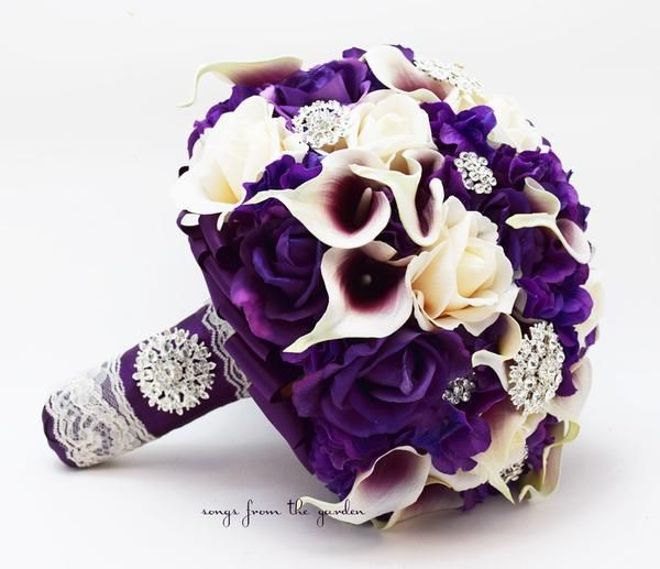 "This lush and lovely bouquet in shades of purple, plum and ivory can be yours to have and to hold on your wedding day! I can create it for you as shown or customize it to fit your color scheme. We can work together to create a custom silk flower wedding package for your entire wedding party! This custom silk flower bridal bouquet is 11"" in diameter and includes Picasso (white with purple center) real touch mini callas, purple real touch roses, ivory real touch roses, and deep purple real touc..."