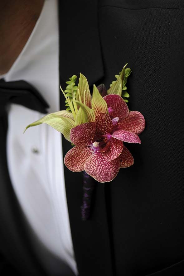 Purple hydrangea, calla lilies and tulips, burgundy cymbidium orchids and kaleidoscope phalaenopsis orchids wrapped in purple silk with bands of rhinestones and pearls. Jonathan Ryan Los Angeles, CA;  Photography: Mike Colón Photographers Newport Coast, CA  http://www.weddingstylemagazine.com/photo-galleries/boutonnieres