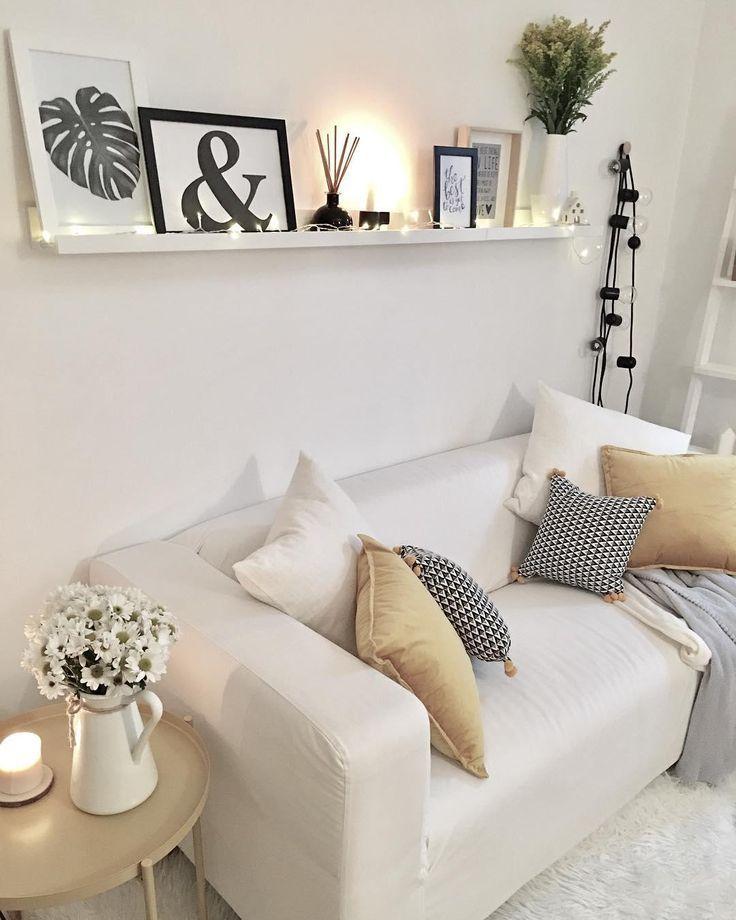 Gemütliches Wohnzimmer mit Lichterkette und Bilde…