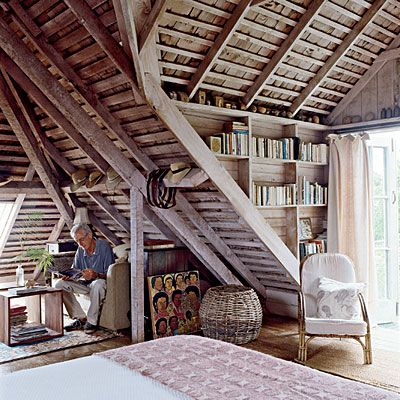 Rustic Beach Attic Bedroom: Small nooks, such as the lounge area and library, make the most of tricky angles in the attic-like master bedroom. Found objects displayed throughout the room give a sense of history to the room. Instead of framing artwork, prop it against walls or shelving for a relaxed point of interest. | CoastalLiving.com