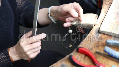 Artisan woman - handmade earrings, grinding and polishing.