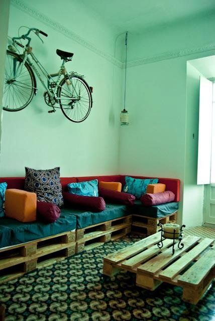 Hanging bike and palet sofa and table. Lamps made with cristal pots and chinese newspaper. At Itinere School and Hostel in Granada. info@itinereschool.com