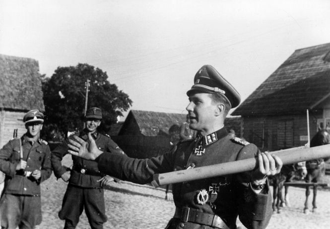 """Estonian SS-Obersturmbannführer Harald Riipalu explains to other SS officers the proper procedure for using a Panzerfaust rocket launcher. Riipalu was decorated with the Knight's Cross on 23 August 1944 for successfully leading the SS Waffen Grenadier Regiment 45 of the Estonian 20th Waffen Grenadier Division der SS in the Battle of Tannenberg Line and in the Battle of Auvere where Riipalu and his regiment drove back the assault of the Soviet Army, which prevented the encirclement of """"Army…"""