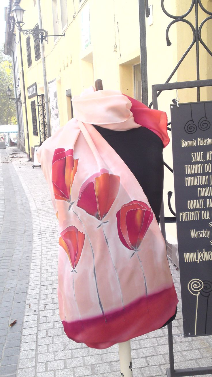 Coral red silk scarf, poppy flowers in brick and clay reds. Presented on bust outside of my workshop. Scarf is wrapped around neck and its end cascades down on torso. Its covering right side of torso, you can see scarf theme very well. Hand painted by SilkAgathe.