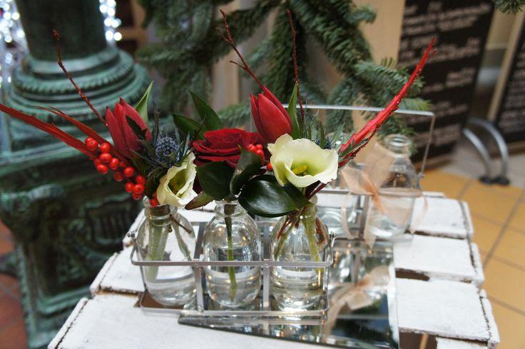 Mini glass milk bottles in a rack with festive flowers