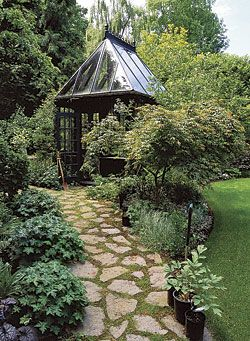 A greenhouse can be both decorative and functional. This Victorian-style greenhouse is the highlight of the garden, positioned at a bend in the path where you can't help but notice it as you move into the yard.