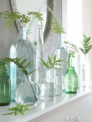 Stems of ferns accent a table or fireplace mantel during the summer. Varied heights and sizes of glass bottles in coastal colors.