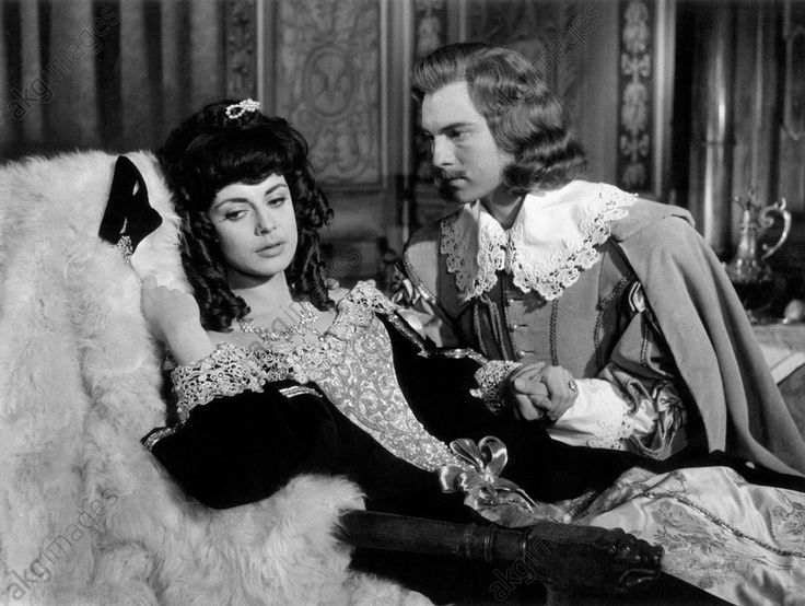 French actor Jacques Toja holding by the hand Italian actress Anna Maria Ferrero lying on a chaise longue in the film Captain Fracasse. France, 1960