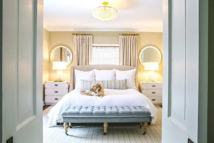 Double doors open to a master bedroom featuring a camel colored bed with silver nailhead trim dressed in soft white shams and duvet placed in front of windows covered in beige gingham curtains layered over bamboo roller shades. A beige wingback headboard is flanked by white campaign nightstands topped with alabaster lamps under round mother of pearl mirrors alongside a blue velvet tufted bench on caster legs placed at the foot of the bed.