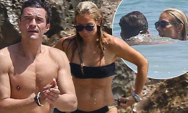 The Pirates Of The Caribbean vet was seen splashing around on the shores of Malibu with a pretty mystery woman who nicely showed off her toned and tanned body in a little black bikini.