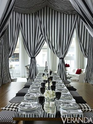 black and white dining table bordered with striped curtains and patterned seats. <3