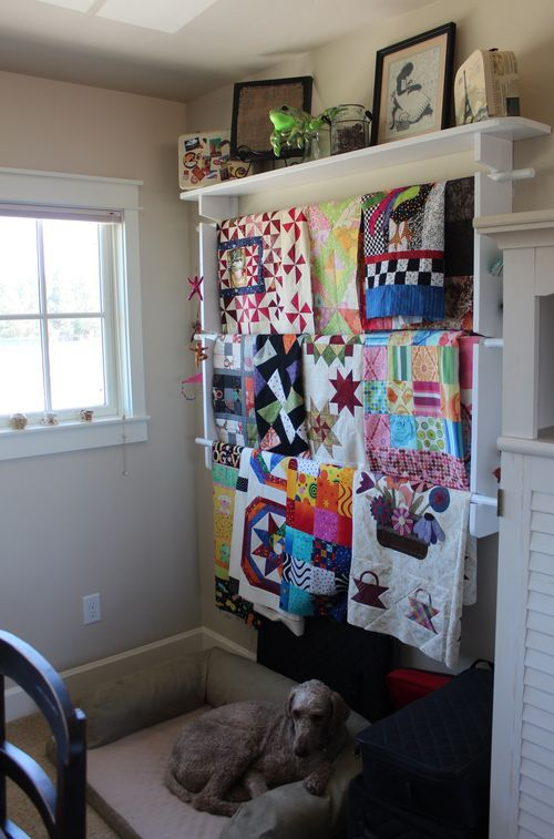 quilt tops on rack - display even if they aren't finished. - great dog too!