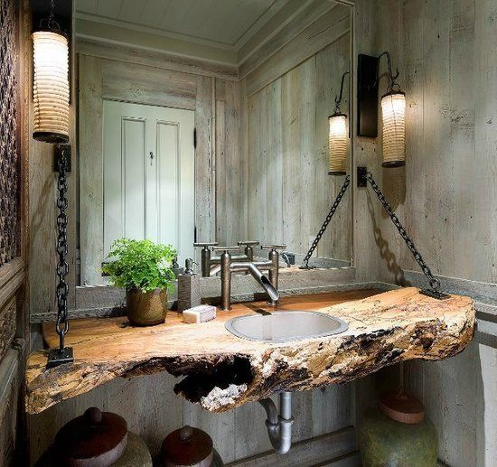 This stunning wall-hung wood shelf with countersunk basin has been cut from a section of tree trunk for the ultimate rustic themed bathroom