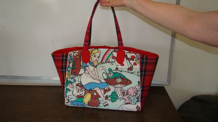 """Front view - vintage (1940) Walt Disney Production """"Alice in Wonderland"""" barkcloth (former curtains) for the main pieces and a red tartan plaid (former skirt) for the side pieces and handles."""