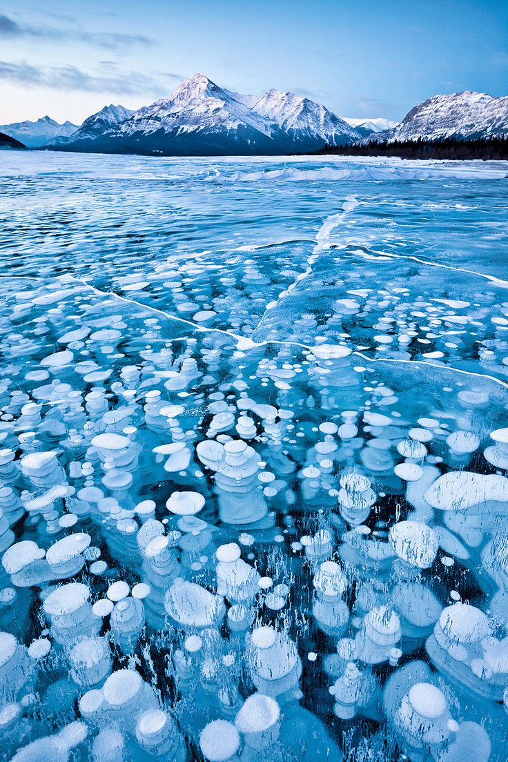 20 UNREAL Travel Destinations! This unique lake in Alberta, Canada, has cool-looking bubbles frozen near the surface. The bubbles are full of frozen methane gas, so quite literally a match could set off an explosion.