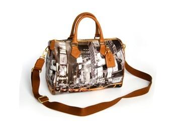 Rigida e spaziosa, ecco la vostra borsa a bauletto!  Portabile sia a mano che a tracolla grazie a dei bellissimi manici in pelle marrone chiaro.  Nel tessuto è rappresentata l'immagine della caotica ma bellissima America.