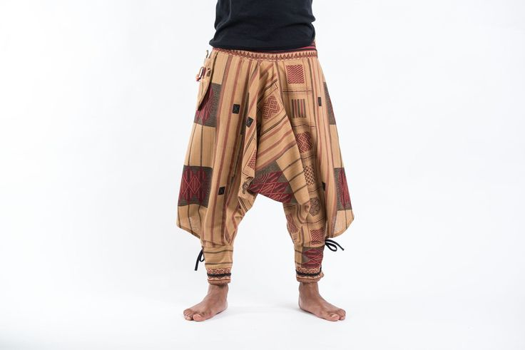 """Amazing Unique Harem Pants made from fairtrade beautiful traditional hill tribe fabric from the North of Thailand. With open-side legs and ankle cuffs with adjustable straps, you can move freely while practicing yoga, doing the split, or chasing butterflies in the mountains of Pai. Suitable for both men and women. Elastic waist on the back allows the pants to fit most sizes. Measurement: Waist: 26""""to 33"""" Hips: up to 42""""  Total length: 35"""""""