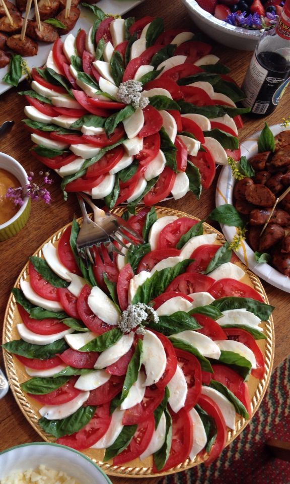 Simple and beautiful caprese plate: tomato slices, mozzarella slices, fresh basil leaves alternated in an eye pleasing pattern, drizzled with olive oil and lightly sprinkled with kosher salt.