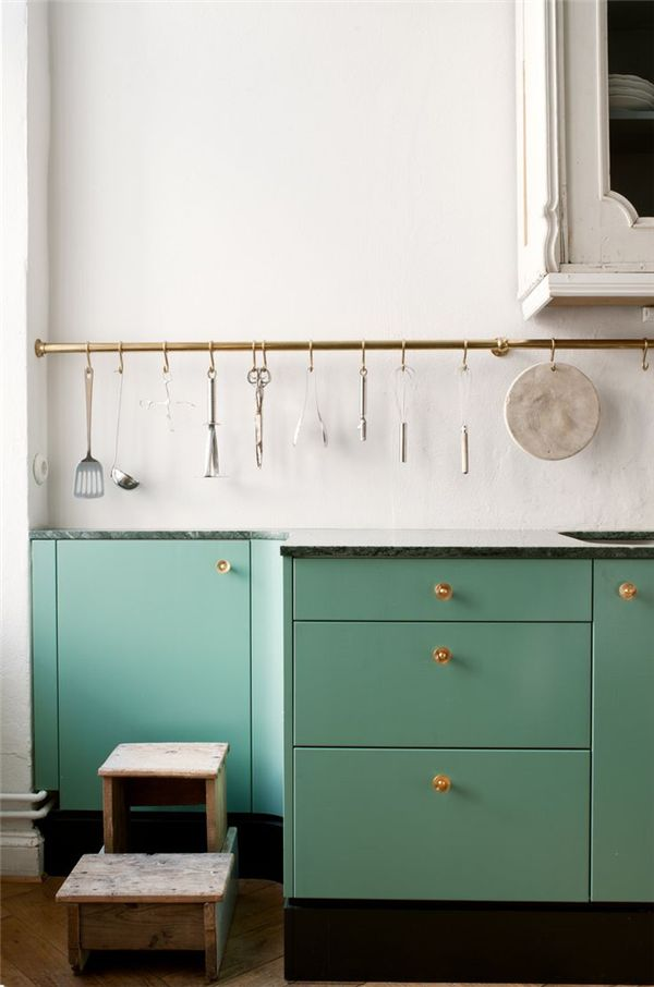 Bottom cabinets in teal/colour and the top and walls in white. Glass knobs.