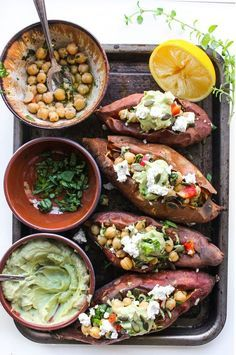 Mediterranean stuffed sweet potatoes with marinated chickpeas and topped with an avocado tahini sauce – grain free & vegan