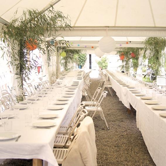 Sfeervolle, landelijke en unieke trouwlocatie in de natuur. Onder witte tenten staan lange tafels met witte tafellinnen voor het bruidsdiner. De tenten zijn aangekleed met kleurrijke lampionnen en planten.