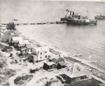 """Point Lookout between 1902-1905. The big paddlewheel craft on the near side of the dock is the """"State of New York"""" which carried freight from Detroit and passengers from Saginaw and Bay City. On the other side of the pier is the """"Flora"""". Off the end is the """"Josie"""". The first cottage was owned by Luther Holland. The second cottage is still owned by the family of former Mayor Dr. George Stewart (Date of this last statement unknown)."""