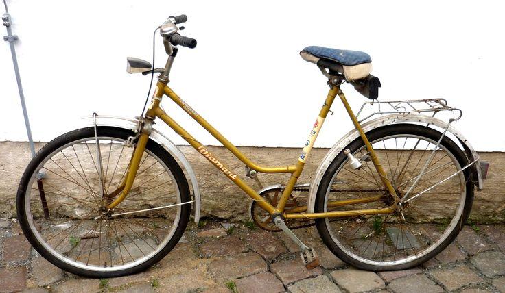 """Fahrrad, """"Diamant""""  Damenfahrrad des Herstellers """"VEB Fahrradwerke Elite Diamant"""" in Hartmannsdorf, in der Nähe des zu DDR-Zeiten Karl-Marx-Stadt benannten Chemnitz. Produziert in den 1980er Jahren, 26 Zoll, Gestell aus Stahl. Felgen, Speichen, Schutzbleche aus Aluminium. Originallackierung in goldgelb, originale Ausstattungsteile des Fahrrades. Sattelauflage blaues Mischgewebe. Kleine schwarze Satteltasche aus Kunststoff für Minimalausstattung an Reparaturwerkzeug."""