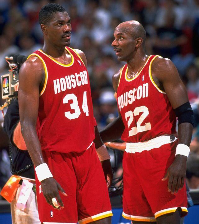 Clyde Drexler and Hakeem Olajuwon talk on the court during Game 2 of the 1995 NBA Finals. Olajuwon celebrates his 50th birthday on Monday. (John W. McDonough/SI)