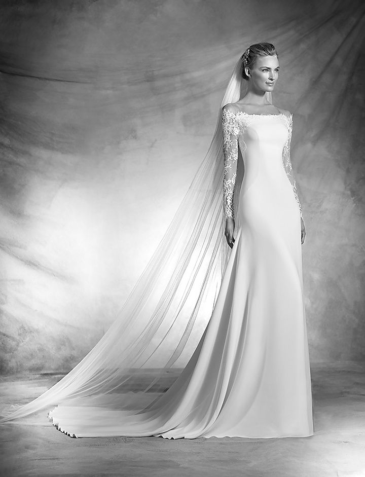 vasily, collectie 2016 Super elegant en vrouwelijk deze trouwjurk voor een slanke bruid. De off shoulder laat de hals en schouders prachtig uitkomen. Alleen van achteren te zien hoe mooi de luxe kant is gecombineerd voor het rugpand en de lange mouwen. De lange sleep en de bijpassende sleep maken het beeld compleet. #exclusief #zijde #couture #atelierpronovias #koonings