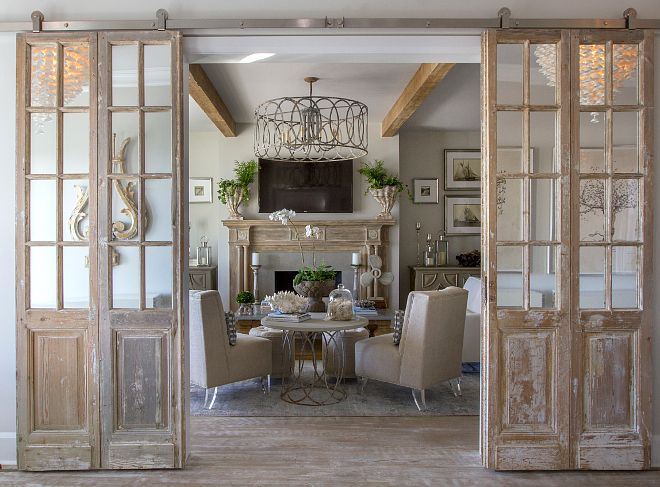 Mirrored antique doors were hung in a barn door hardware in the formal living room to bring character and patina. The pale pine vintage mirror door set also features a whitewashed finish.