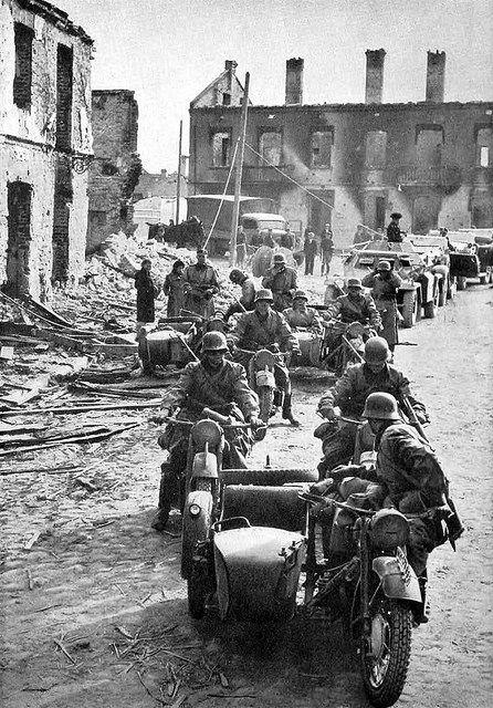 En alguna ciudad de Polonia durante la invasión, una columna de vehículos encabezada por motocicletas BMW R-75 hace una parada en una calle devastada por los bombardeos aéreos.