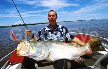 Angler aboard a charter boat with a  large barramundi (48 lb) caught in Top  End waters. Recreational fishing with  Obssession Fishing Safaris. Photographer:David  Hancock/Copyright:SkyScans. Stock Photo By David C Hancock