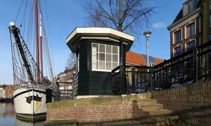 """Brugwachtershuisje A-brug Groningen.. Het houten brugwachtershuisje werd gebouwd rond 1925. Het is ontworpen door S.J. Bouma (1899-1959) uit de Amsterdamse School, die van 1924 tot 1942 gemeentearchitect van Groningen was. Het brugwachtershuisje is aangewezen als gemeentelijk monument """"vanwege zijn betekenis voor de geschiedenis van de infrastructuur van Groningen"""", evenals de identieke brugwachtershuisjes bij de Bontebrug, de Oliemuldersbrug en halverwege de oostzijde van de Turfsingel."""