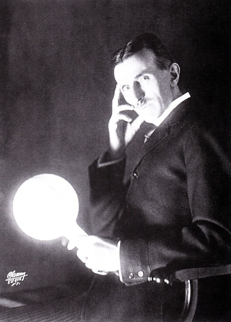 """Tesla with one of his famous """"wireless"""" lamps. Published on the cover of the Electrical Experimenter in 1919."""