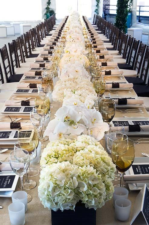 All white arrangements of hydrangeas and orchids give texture to this single, long table at a wedding reception.