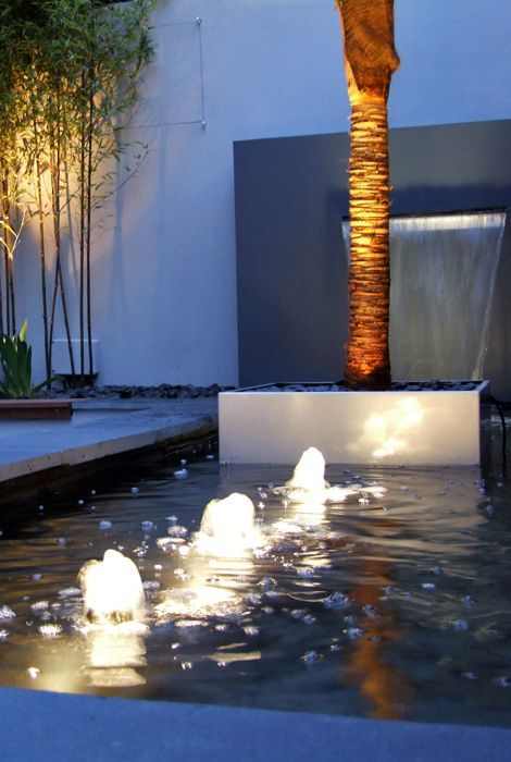 Palm tree in a #pool with bubble fountains and waterfall in a #modern London #garden