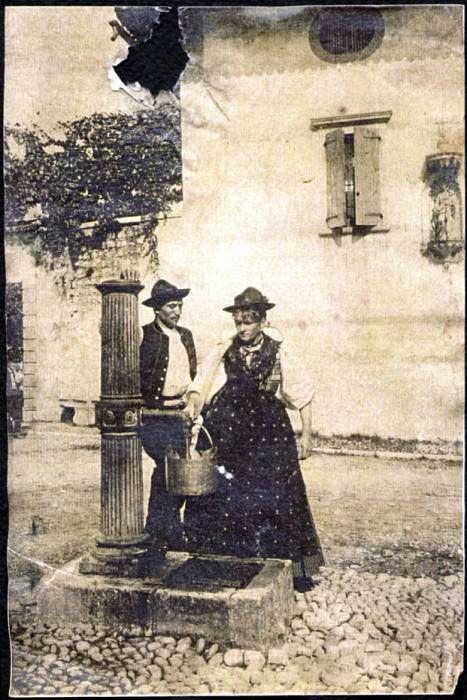 Nella piazza di Castello di Aviano una coppia posa accanto alla fontana. La donna riempie d'acqua un pentolone. La coppia indossa gli abiti tipici della zona. Alle loro spalle il palazzo Fabbris. La fotografia fa parte della collezione privata della Biblioteca comunale Monsignor Lozer [SIRPAC - Scheda F 33890]