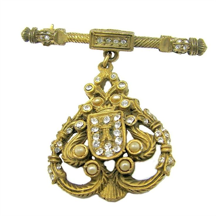 """Jerry DeNicola's ornate regal shield brooch done in the style of a Georgian era banner carried before royalty encrusted with precious stones; this one is from his 1950's the """"The Real Look Collection"""" and abounds with rhinestones and faux seed pearls as well as castles, crowns, ferns, columns and more from brendastreasures on rubylane.com!"""