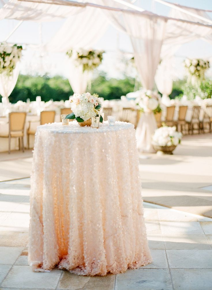 An accent table is swathed in a rosy sequined tablecloth. #outdoorwedding #sequin #tablecloth Photography: KT Merry Photography. Read More: http://www.insideweddings.com/weddings/a-gorgeous-and-elegant-outdoor-florida-wedding/536/