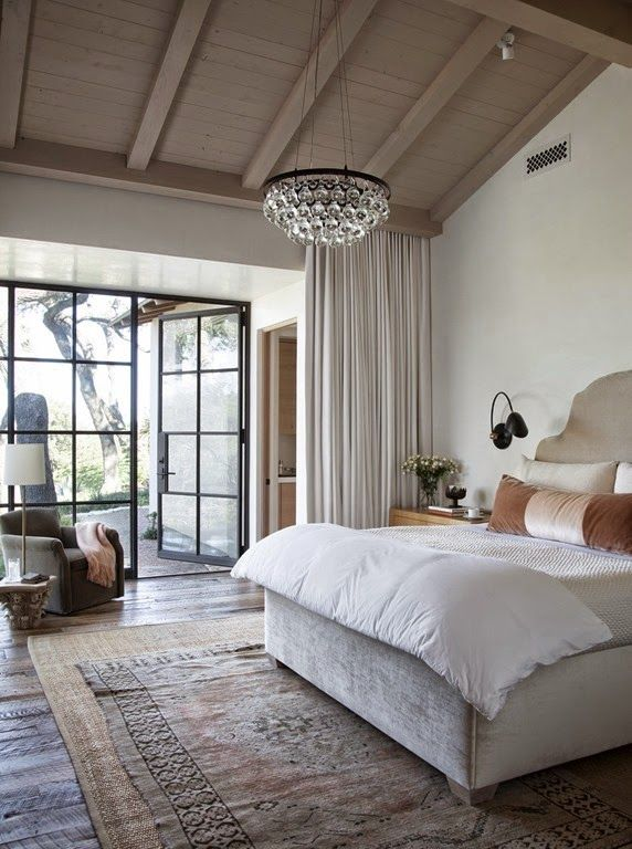 bed room shades of neutrals. crystal chandelier. Linen headboard. velvet pillows. floor to ceiling curtains.