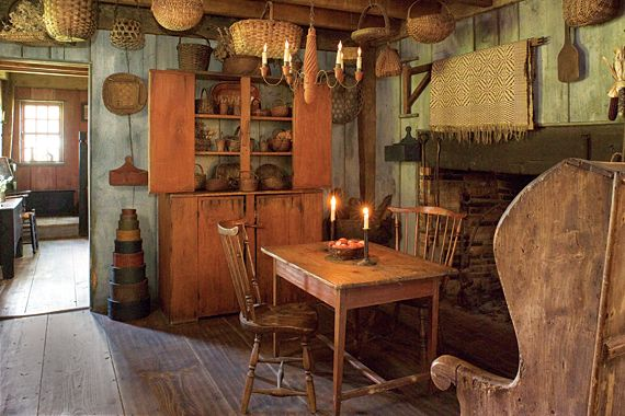 The fireplace in the keeping room was made with bricks removed from a 1728 Connecticut house. A rare, early blanket crane, holding a period coverlet, hangs above the fireplace. The only related example the couple had ever seen was offered by the late Pat Guthman in 1993. The adjacent curved back early nineteenth-century pine settle was found in a shop along Route 7 in Connecticut. Some examples from the wife's large collection of baskets can be seen in a red painted cupboard purchased from…
