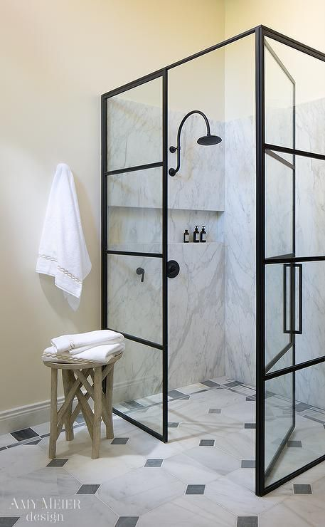 Fabulous master bathroom boasts a glass and steel shower enclosure filled with a gray and white marble surround fitted with an oil rubbed bronze gooseneck rain shower head over a tiled shelf niche as well as a marble shower floor accented with gray diamond inlays.