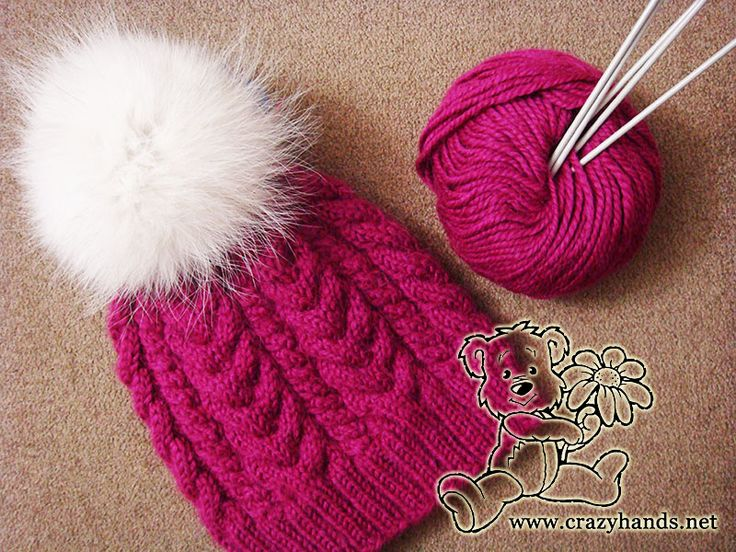 Wine knitted hat with white fur pom pom, skein of yarn and two needles