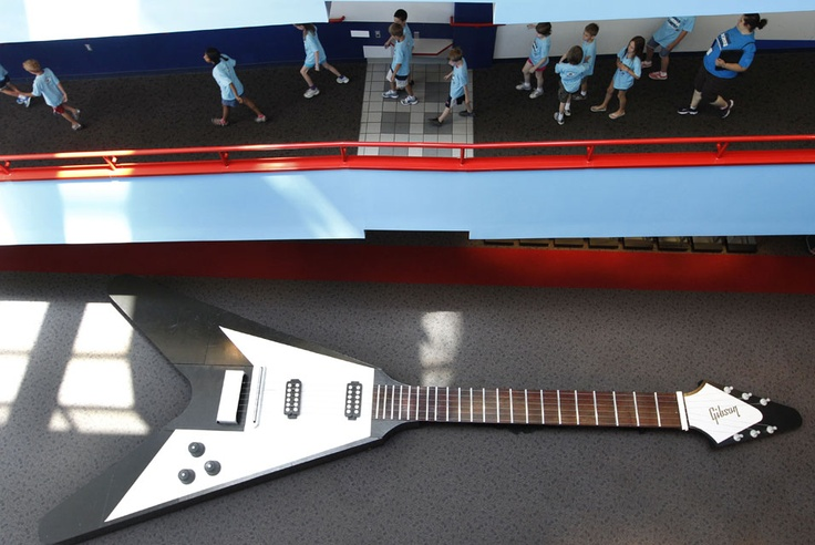 Children visiting the Carnegie Science Center in Pittsburgh, Pennsylvania, walk past a 40-foot-long working model of a 1957 Gibson Flying V electric guitar which is on display as part of the National Guitar Museum exhibition on June 26, 2012.